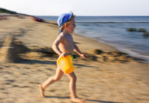 Usedom, boy runs with little bucket on the beach,