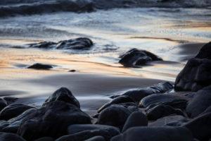 Steine am Strand Praia da Arrifana im Abendlicht, Atlantischer Ozean, Aljezur, Costa Vicentina, Algarve, Distrikt Faro, Portugal