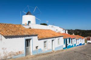 Windmühle und bunte Häuser in Odeceixe, Costa Vicentina, Algarve, Distrikt Faro, Portugal
