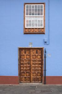 Blaues Wohnhaus mit hölzener Eingangstüre mit Ornamenten in der Calle San Agustin, San Cristobal de La Laguna, Teneriffa, Kanarische Inseln, Spanien