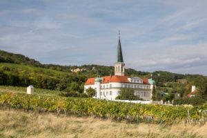 Das Schloss Gumpoldskirchen (Beherbergungsbetrieb und Seminarhotel) mit Pfarrkirche St. Michael umgeben von Weinbergen, Gumpoldskirchen, Niederösterreich, Österreich