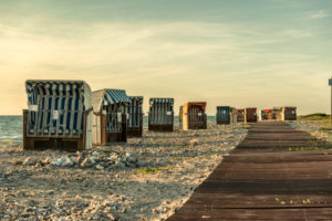 Wallnau, island of Fehmarn, Ostholstein, Schleswig-Holstein, Germany. Beach chairs on the beach of Wallnau in the evening light.