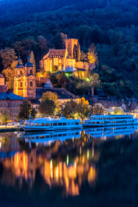 Miltenberg on the Main, Bavaria, Lower Franconia, Mildenburg and parish church of St. James with excursion boats on the Main at dusk