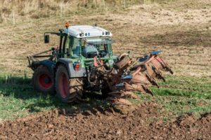 Breuberg, Hessen, Germany, farmer with tractor while plowing.