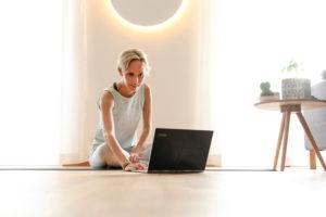 Frau 40+ praktiziert Yoga zuhause mit Notebook. Online Yoga Kurs.