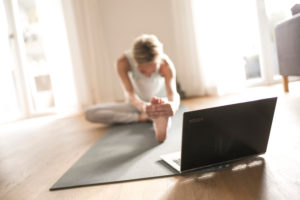 Woman 40+ practices yoga at home with notebook. Online yoga class.