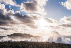 Rocky beach with wave break, evening sun and cloud play, winter in Greece, island Proti in the background
