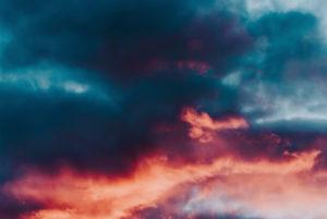 Red evening sun in clouds, blue red clouds