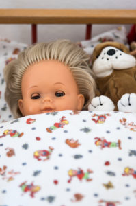 Doll and soft toy in a doll's bed