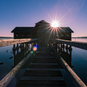 Winter afternoon on the Ammersee / Lake Ammer, Germany, Bavaria, footbridge, shipping stage, boat house, sun, backlight