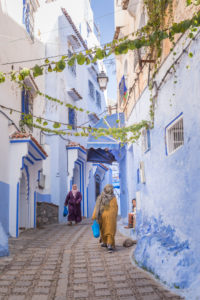 Pedestrians in a blue alley in Chefchaouen, Morocco, North Africa, Africa