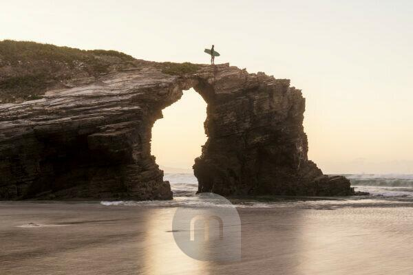 Spain, north coast, Galicia, national park, cathedral beach, Playa de las Catedrales, surfer with board on rocks