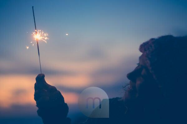close up of woman looking at sparkler the night of the new year at the evening alone and lonely - lady playing with sparkler outdoors