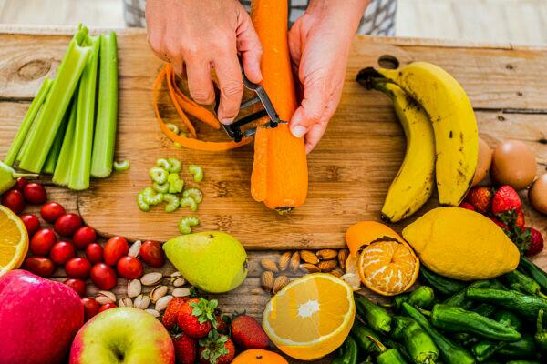 Close up of woman adult hands cutting fresh seasonal healthy carrot and mixed vegetables for health lifestyle food and diet weight loss activity at home