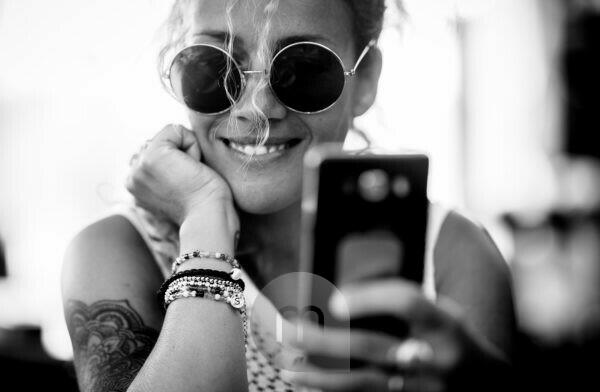 Black and white beautiful adult caucasian alernative trendy woman portrait - cheerful and smile lady with tatto doing selfie picture or video call with mobile phone