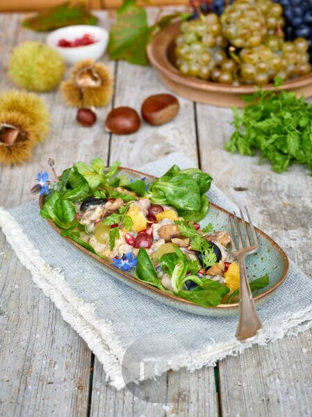 Chestnut salad with grapes, orange, lamb's lettuce and pomegranate in an elongated bowl on a cloth, untreated wooden table with chestnuts, peels and chervil