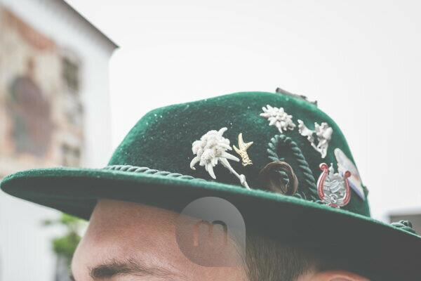 Der Kopf eines Mannes mit bayrischem Trachtenhut und einzelnen Ansteckern und Glücksbringern drauf.
