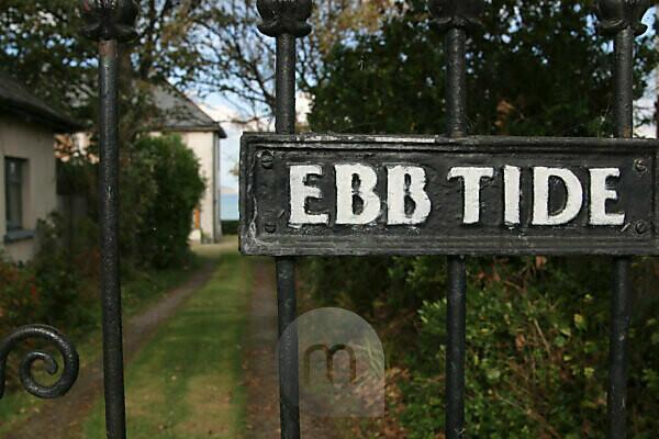 Einblick in Garten mit Schild an Tor Ebb Tide in Irland