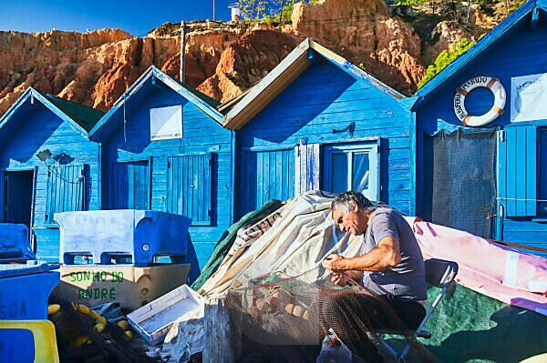 Europe, Portugal, Algarve, Litoral, Barlavento, Faro district, near Albufeira, Praia dos Olhos de Agua, fishermen mending nets, blue fishermen's huts off the red-brown cliffs