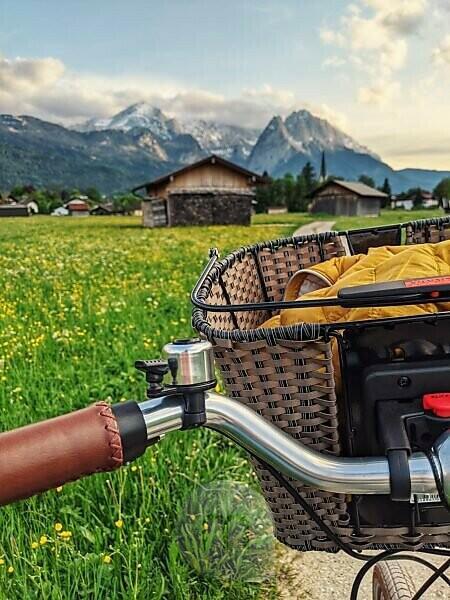 Nahaufnahme von Fahrradlenker und Fahrradkorb, im Hintergrund die Zugspitze im Frühling