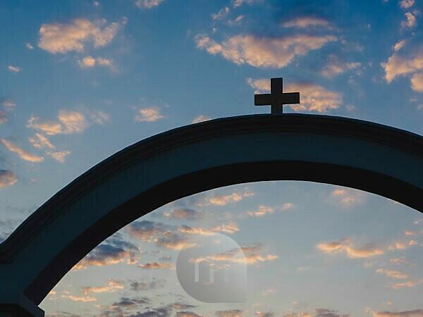Church cross in Oia on Santorini in Greece at sunrise