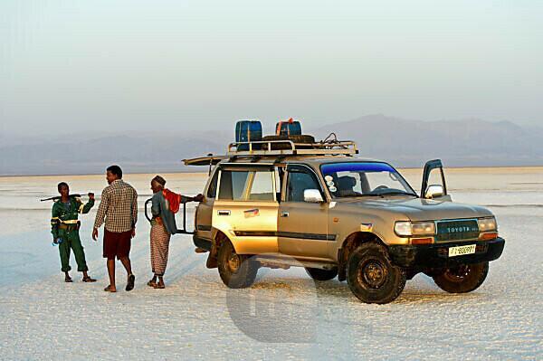 Lokaler Führer, Fahrer und Wachmann stehen neben einem Allradfahrzeug einer lokalen Tourismfirma auf der Salzkruste des Assale Salzsee, Hamedala, Danakil Senke, Afar Region, Äthiopien