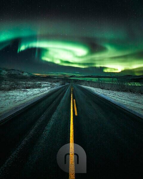 Norldichter über einer langen, geraden Straße bei Kilpisjärvi, Lappland, Finnland