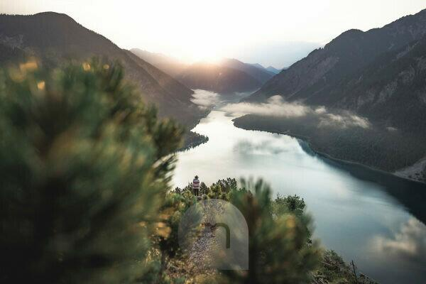 Sunrise over the Plansee in Austria taken from a hunter's path with a woman in the background