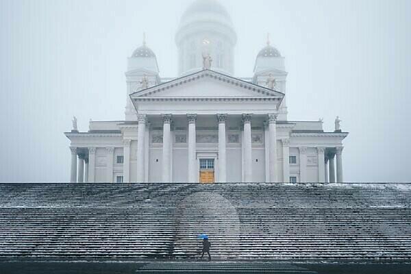 Eine Frau mit blauem Regenschirm im Nebel / Regen vor dem Dom in Helsinki, Finnland