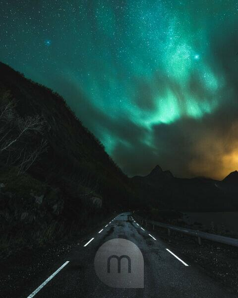 Northern lights over the fjords of Senja island in Norway. A road leads into the dark