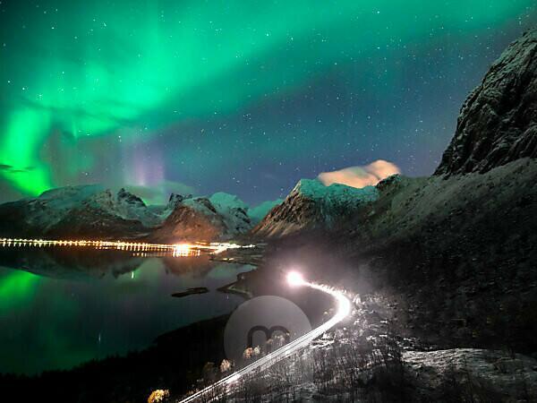 Nordlichter über Bergsbotn auf der Insel Senja in Norwegen bei Nacht. Ein Auto fährt währenddessen über eine Straße, im Hintergrund schneebedeckte Gipfel