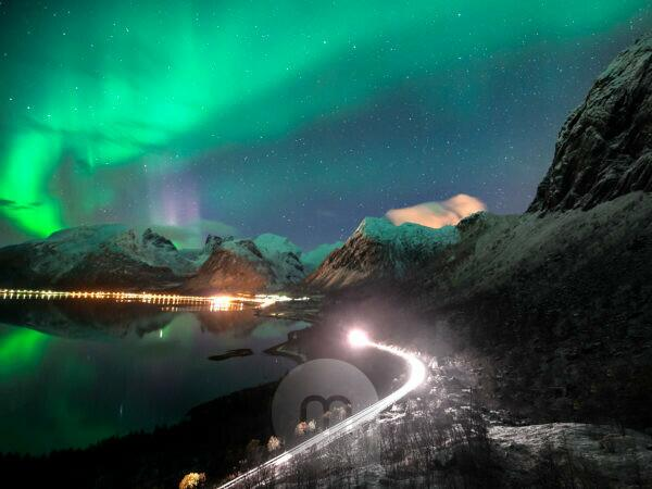 Northern lights over Bergsbotn on Senja island in Norway at night. Meanwhile, a car drives along a road with snow-covered peaks in the background