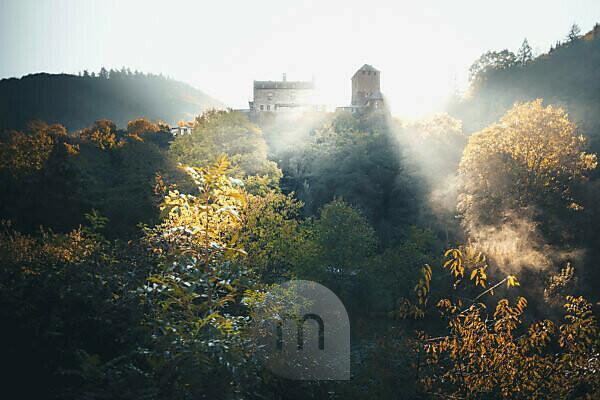 Autumn sunrise over an old castle with sunbeams in the Hunsrück