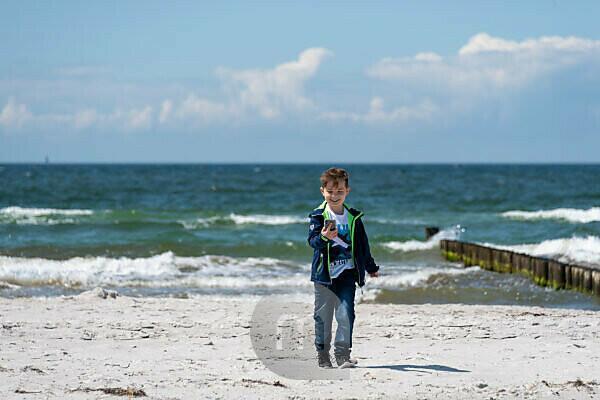 Junge läuft mit Handy lachend am Strand entlang