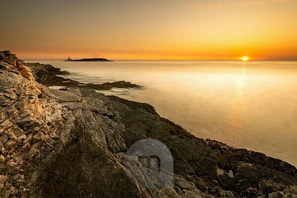 Abendlicht mit Sonnenuntergang am Ufer des Mittelmeeres auf Kap Kamenjak in Istrien, Kroatien. Schroffe Felsen, durch Langzeitbelichtung glattes Wasser und im Hintergrund eine kleine Insel mit Wolken wie einem Vulkan.