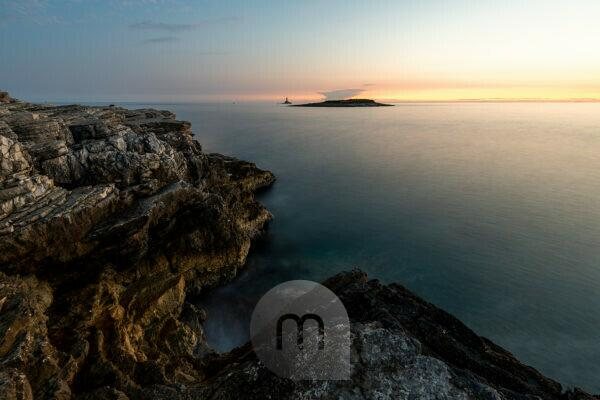 Evening light on the shores of the Mediterranean Sea on Cape Kamenjak in Istria, Croatia. Rugged rocks, long exposure to smooth water and a small island with clouds like a volcano in the background.