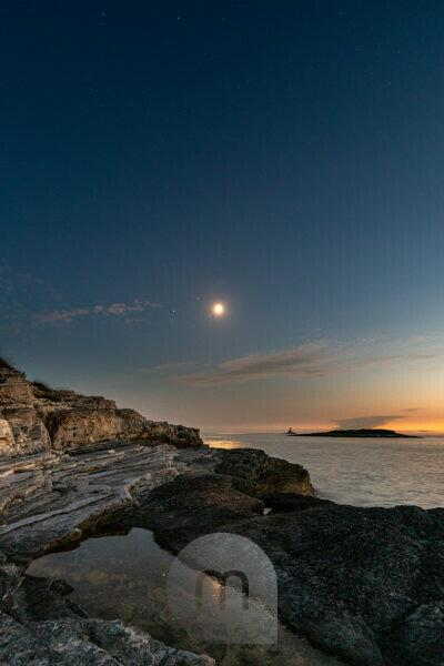 Full moon in the Mediterranean on Istria on the Croatian coast. In the background a small island, in the foreground the rocks of Cape Kamenjak