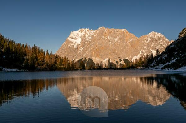 The Wetterstein Mountains with Zugspitze are reflected in the clear water of the Seebensee near the Tyrolean hut