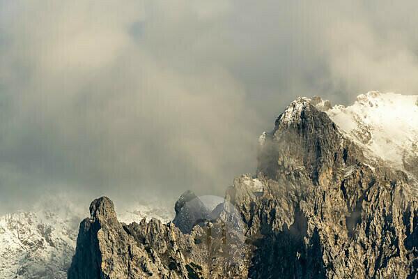 Die Viererspitze im Karwendel, im Hintergrund der Wörner bei Schnee im warmen Abendlicht mit dramatischen Wolken