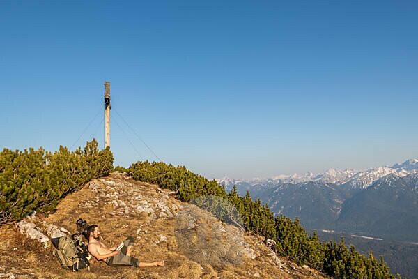 Bergsteiger während Gipfelpause auf dem Simetsberg, genießt die Aussicht auf das Karwendelgebirge neben dem Gipfelkreuz