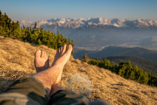 Relaxed break at the summit for mountaineers - feet with a view of the Karwendel, taken on the Simetsberg in the Ester Mountains