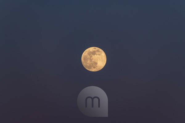 Full moon against a purple blue sky
