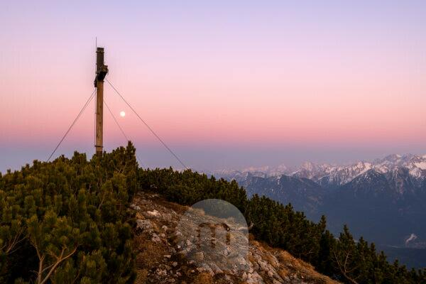 Simetsberg summit cross and in the background Karwendel and Estergebirge with a full moon in the evening after sunset