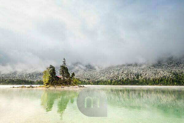 Eine kleine einsame Insel mit einer Blockhütte und rotem Dach, mitten im wunderschönen Eibsee unterhalb der Zugspitze in den bayrischen Alpen des Wettersteingebirges während den Eisheiligen - Neuschnee im Hintergrund auf dem Wald und Wolkenstimmung.