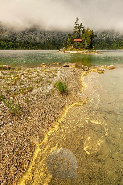 Gelber Pollen von Nadelbäumen treibt am Ufer des Eibsee im Wettersteingebirge im Frühling. Im Hintergrund eine kleine Insel mit Blockhütte und rotem Dach, sowie Schnee auf dem Wald und bedeckter Himmel.