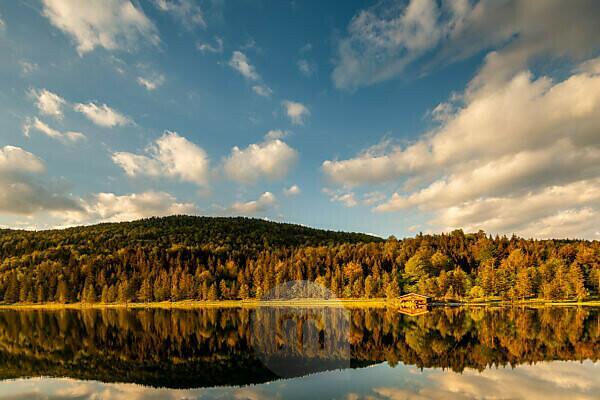 Das Bootshaus am Ferchensee im warmen Abendlicht der untergehenden Sonne im Frühsommer. Eine perfekte Spiegelung unterstreicht die Wolkenstimmung und schönen gold-braunen Farben des Waldes, im Hintergrund der hohe Kranzberg.