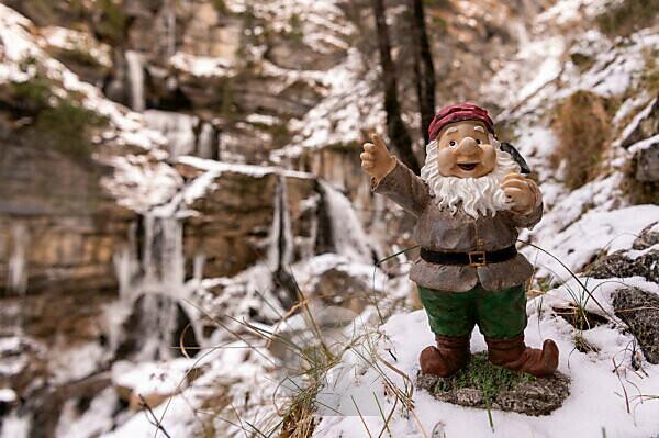 Ein entlaufener Gartenzwerg steht im Schnee bei den Kuhflucht Wasserfällen nahe Farchant. Wie er dort hinkam, bleibt ein Rätsel.