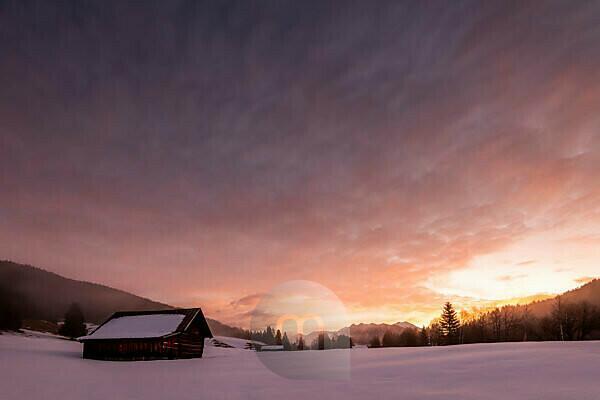Heuschober bei Sonnenaufgang. Bunte farben am himmel, im Hintergrund die Soierngruppe des Karwendel, im Vordergrund ein Heuschober, aus niedriger Position fotografiert.