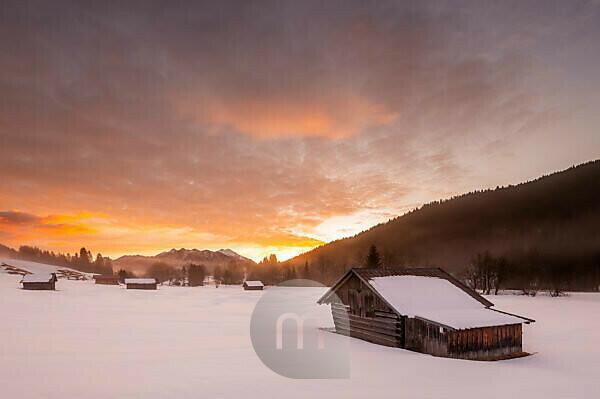 Morgenrot im Werdenfelser Land. Einige Heuschober stehen im frischen Schnee, während im Hintergrund die Soierngruppe des Karwendel, die Landschaft des Gebirge betont.