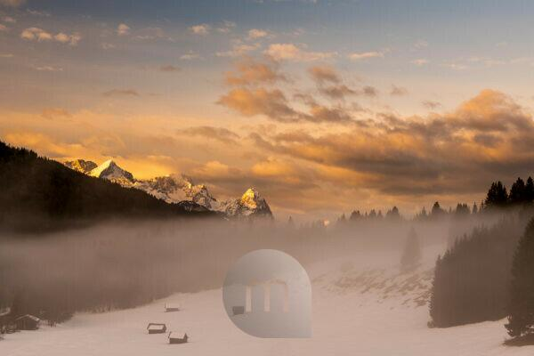 Zugspitze, Alpspitze and Wetterstein Mountains in the early morning. In the foreground a few small haystacks, wooden huts and fog, while the dawn bathes the snowy landscape in warm orange tones.